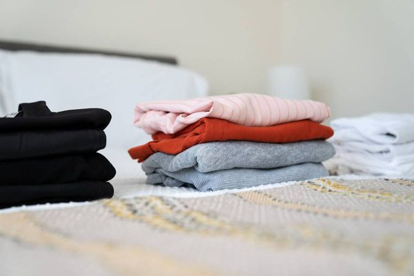 Three piles of laundry sorted into darks, colours, and whites, folded on a bed
