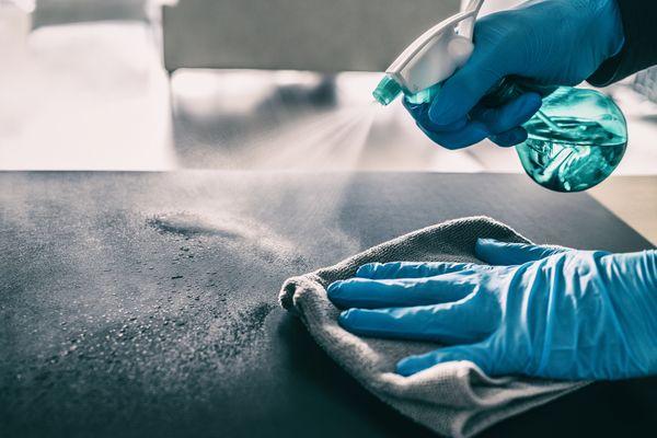 pessoa limpando a bancada com água sanitária