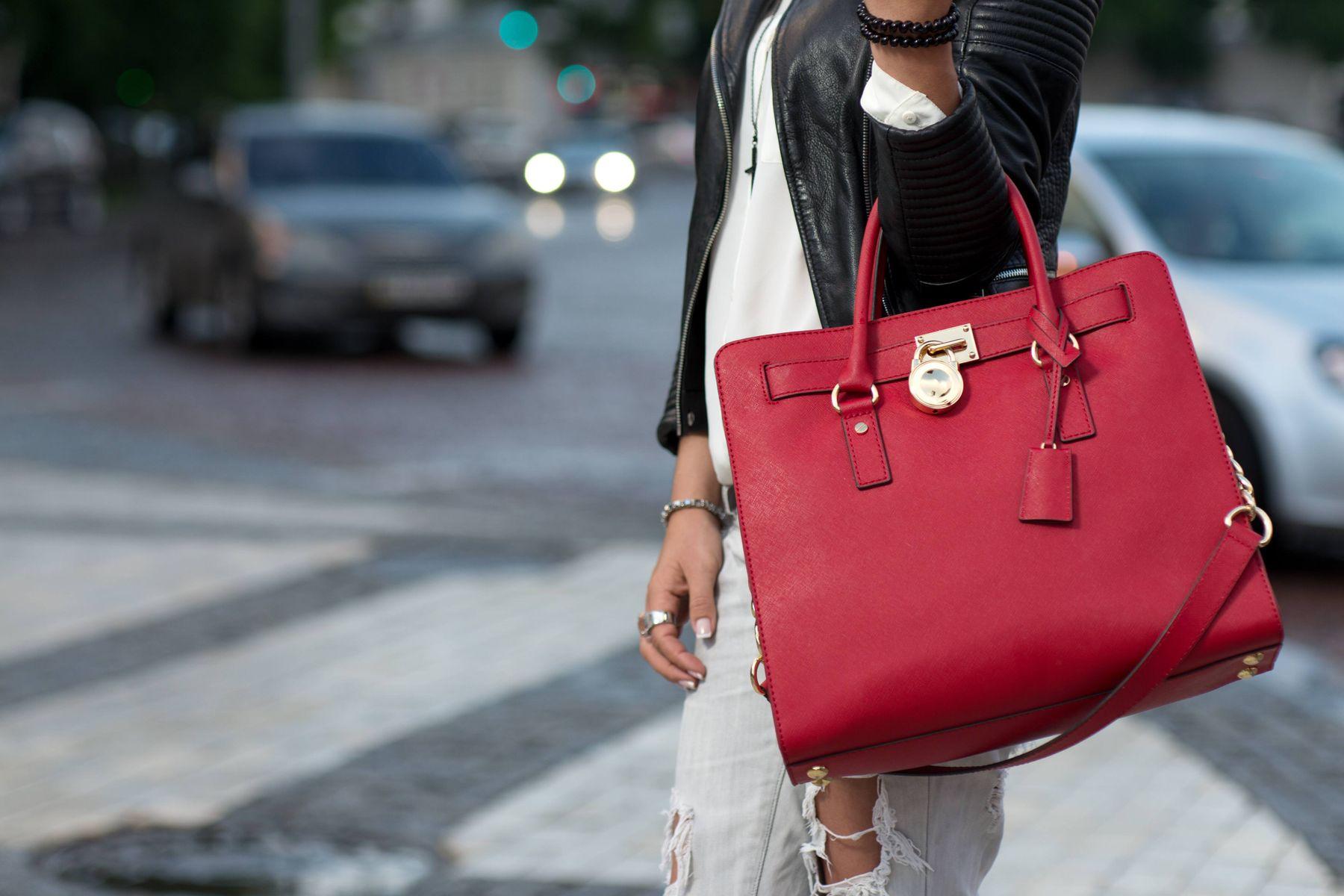Mulher na rua com vestido branco e jaqueta de couro preta e bolsa vermelha de couro