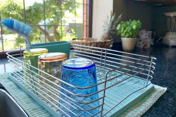 Copos de vidro colorido secando no escorredor sobre a bancada