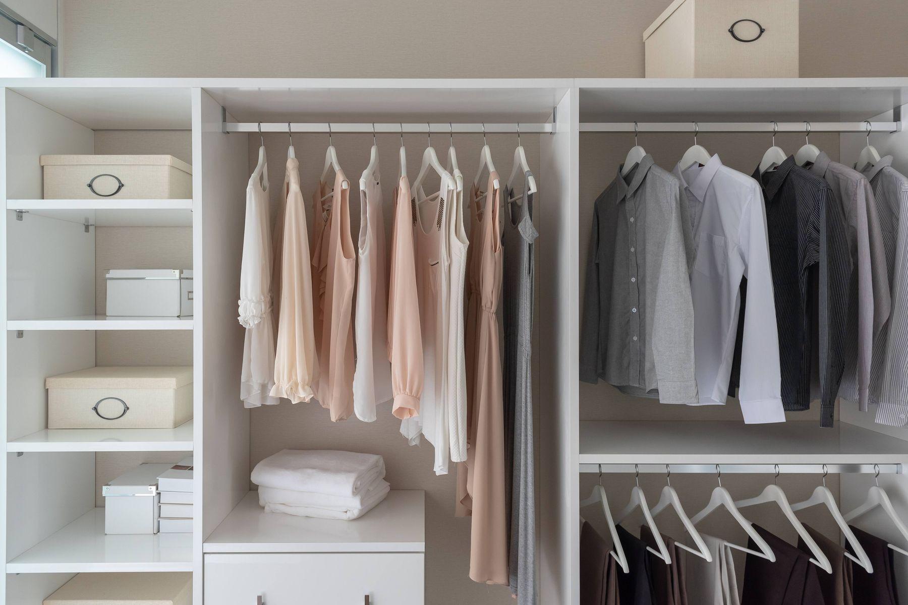 Guarda-roupa branco com três divisórias, com camisas, vestidos e calças pendurados em cabides, toalhas brancas de banho dobradas e caixas