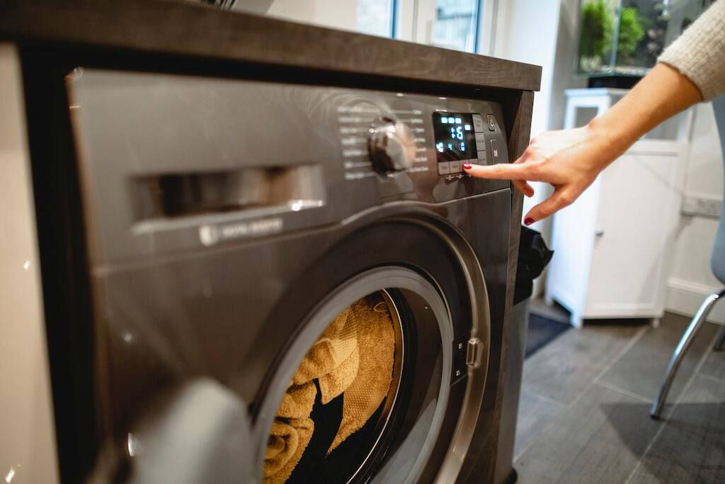 En kvinnohand trycker på en knapp på en självdoserande tvättmaskin med ett välmanikyrerat finger