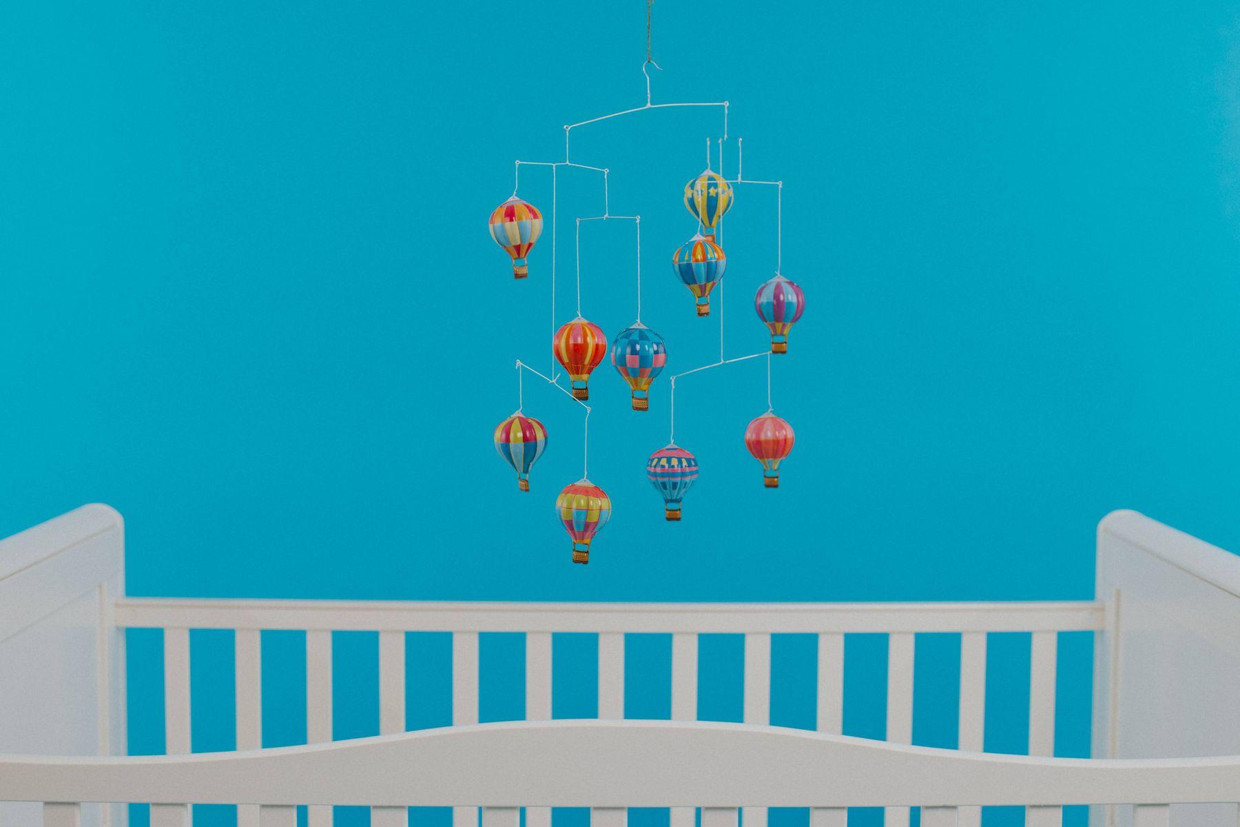 kleurrijke ballonnen mobiel bovenop een wieg in een blauwe kamer