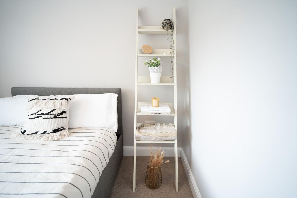Estante organizada ao lado de uma cama de solteiro
