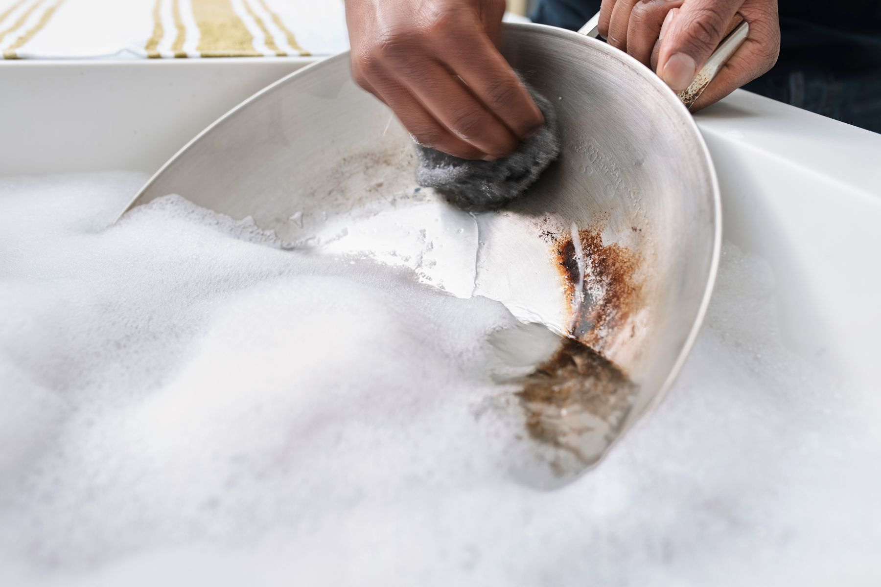 Step 1: person scrubbing rusty wok with a steel wool pad