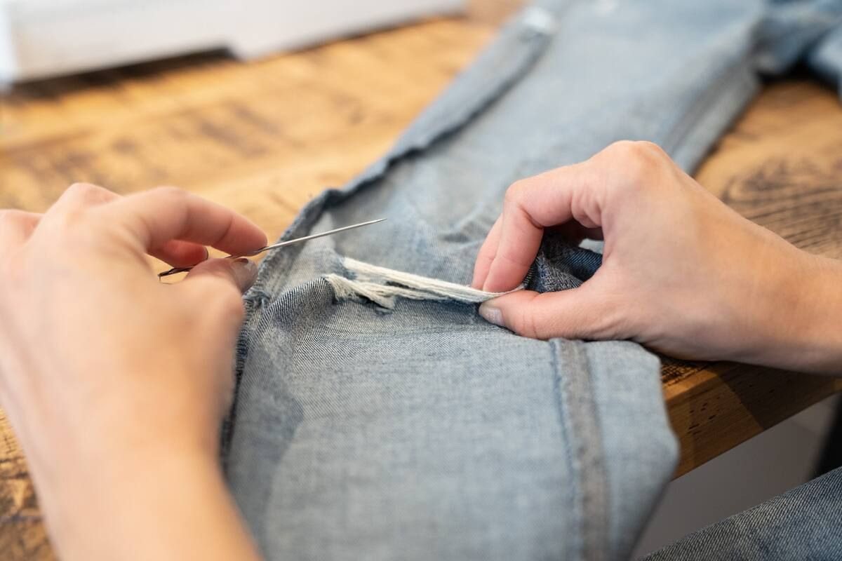Using a needle and thread to stitch a tear on a pair of jeans.