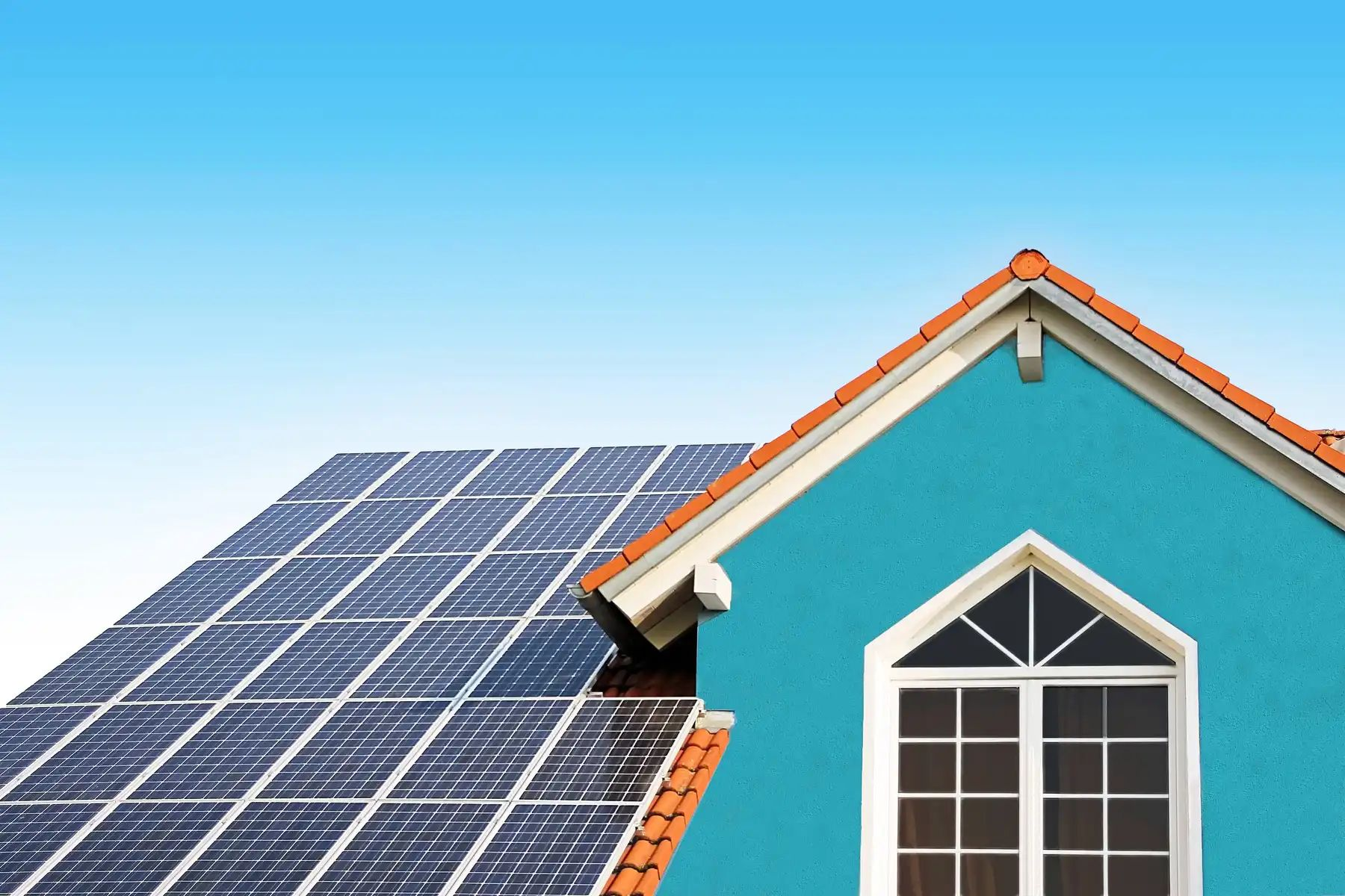The roof and top of a blue house with solar panels and blue sky in the background