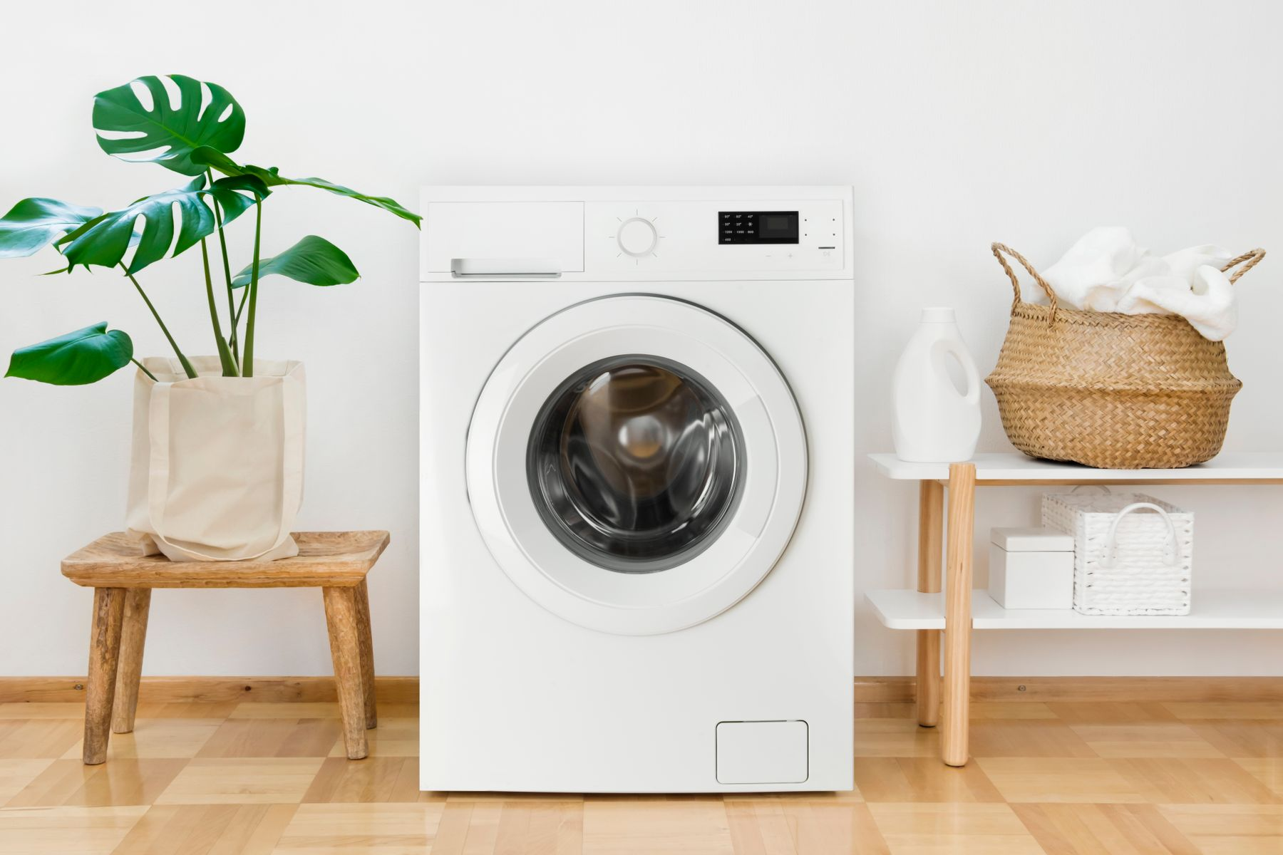 clean white washing machine next to a plant and some white fresh laundry