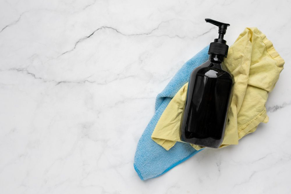 Cloths and a bottle of washing up liquid on top of a marble countertop
