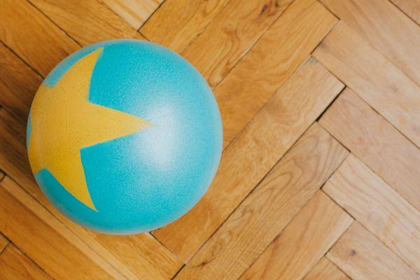 Bola azul e amarela em cima de piso de madeira limpo e brilhante