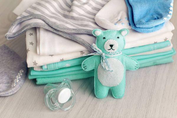 Urso de pelúcia verde encostado em roupinhas de bebê dobradas