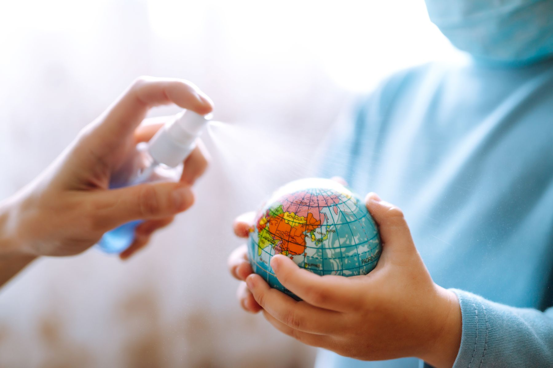 person spraying cleaning solution on a little toy globe held by a child