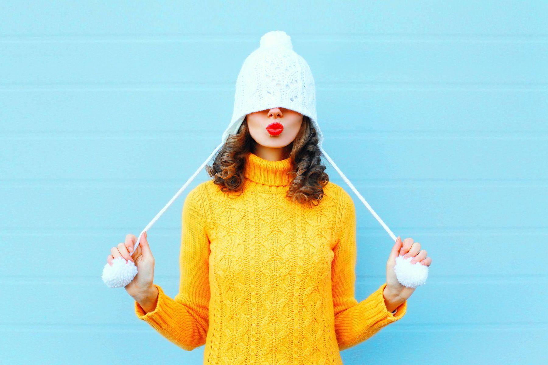 Frau mit Strickpulover und Strickmütze streckt zunge heraus