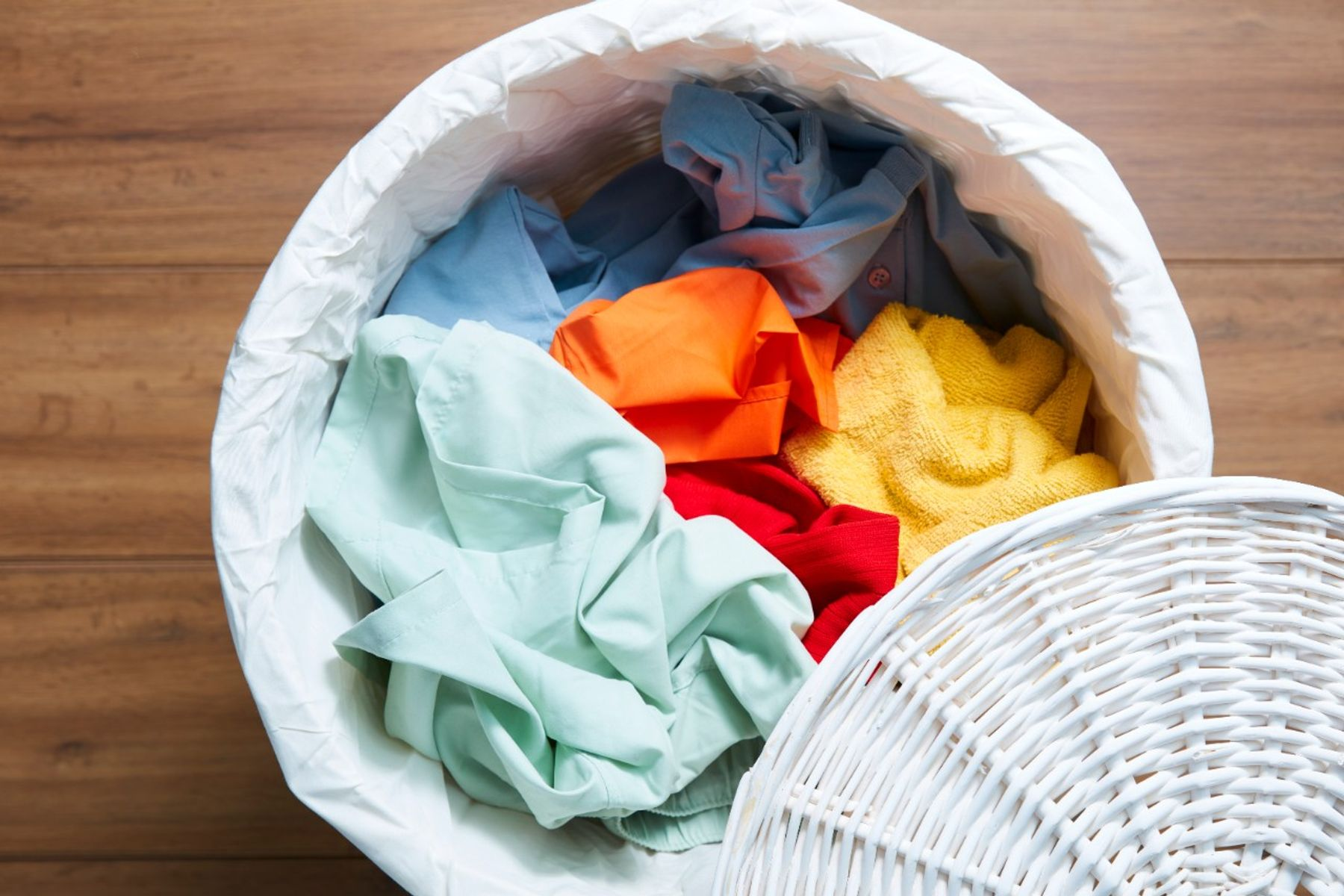 A pile of coloured clothes that smell damp after washing in a white laundry basket